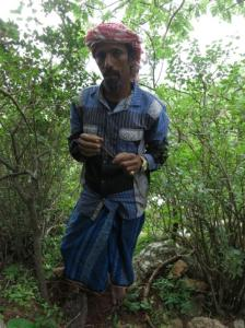 Abu Maryam holds a root traditionally used by Soqotri Bedu for cleaning the teeth. He wears a cotton shirt, blue furtah, Jordanian keffiyeh, Chinese counterfeit watch