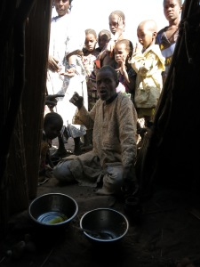 Locals in the village of Daari chatter in Fulani, gathered outstide my stick-built tent