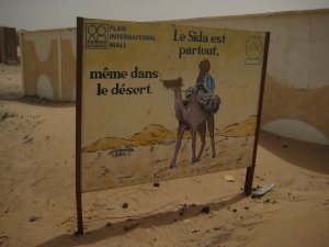This sign captures the Timbuktu experience of recent. A sign warning travelling cameleers of the dangers of AIDs, the faces of the camel and rider were spray-painted over by the djihadistes during their reign over the town