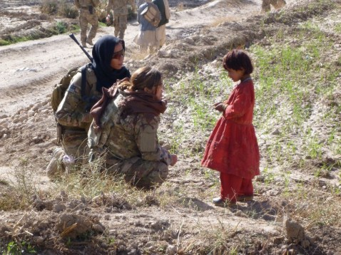 Female CST-2 member speaks with Afghan child